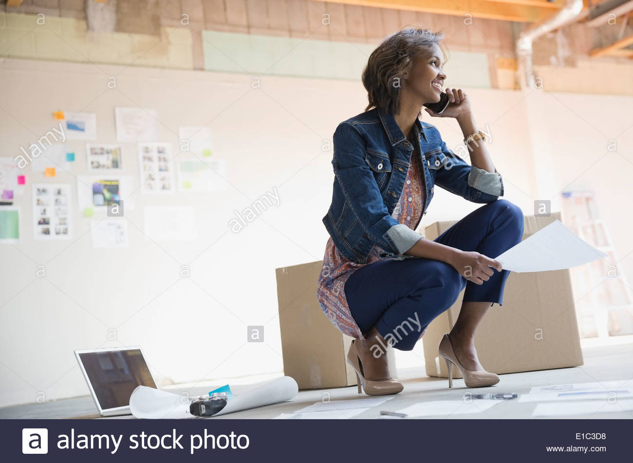 Businesswoman talking on cell phone in new office Stock Photo