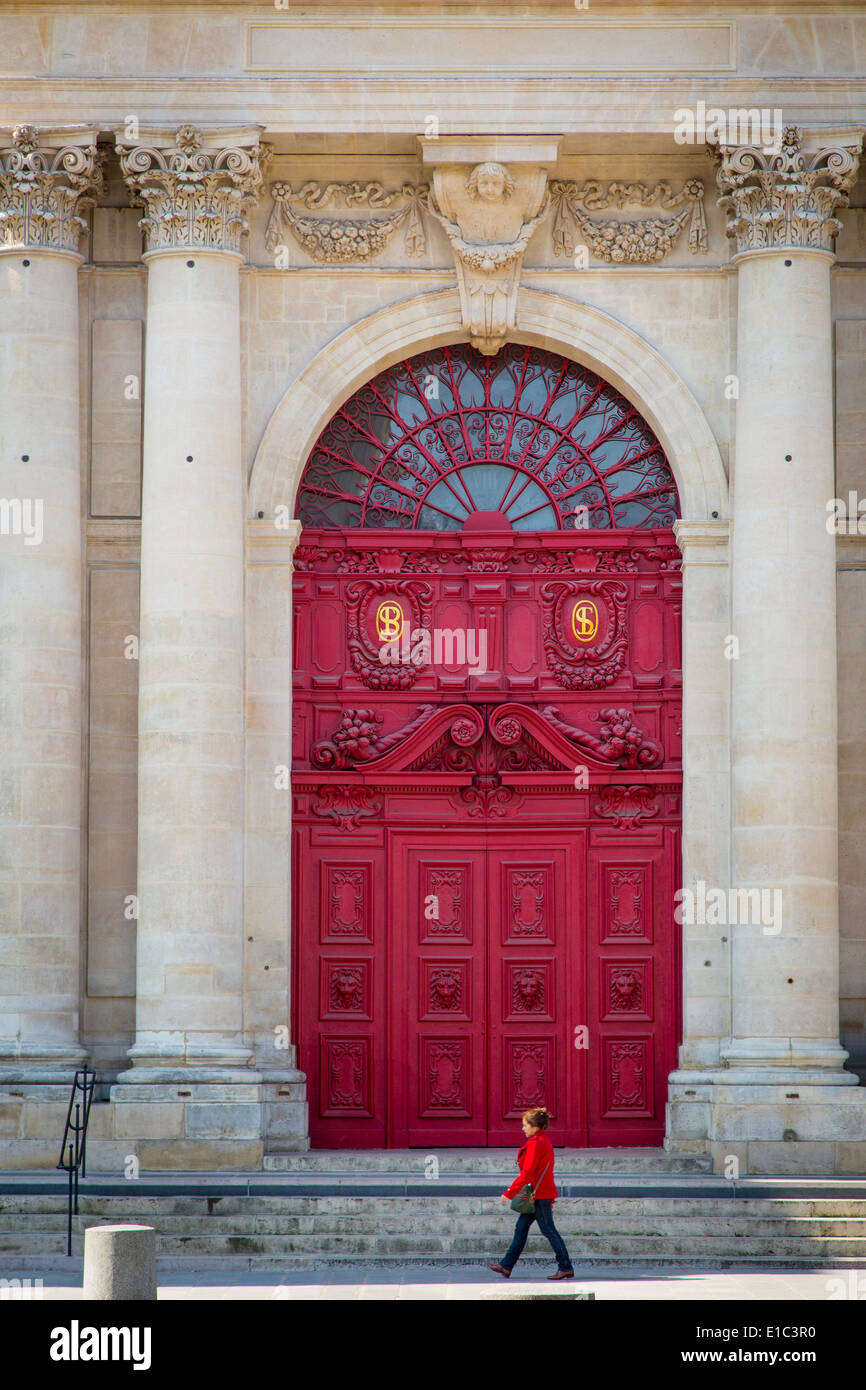 Woman walks past the front doors to Saint Paul - Saint Louis Church in the Marais, Paris France - Stock Image