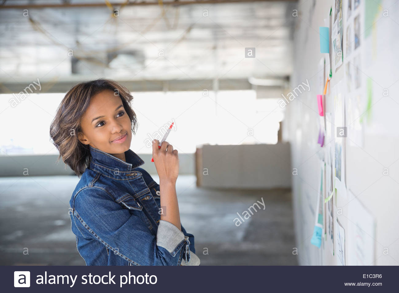 Confident businesswoman brainstorming at board in new office - Stock Image