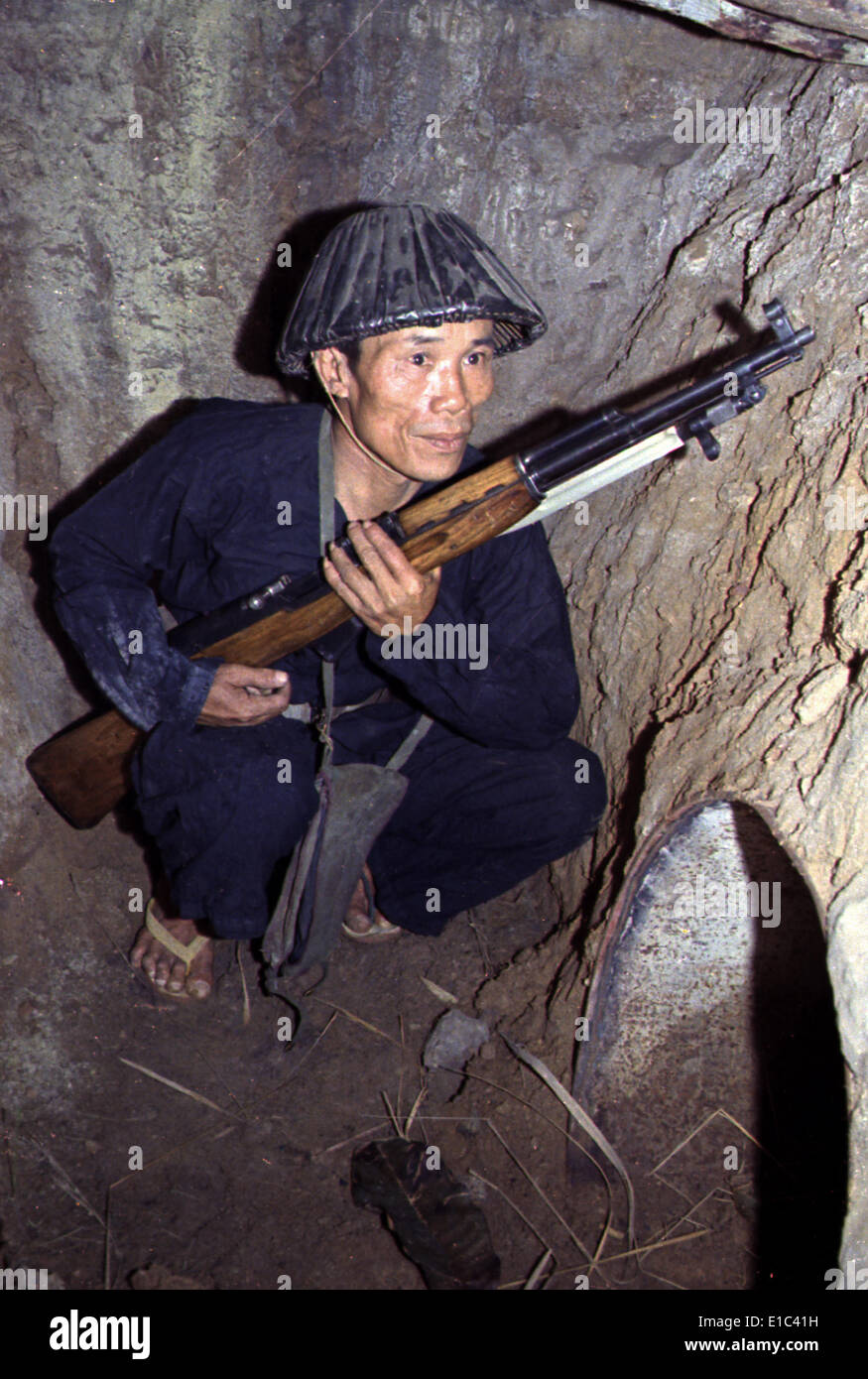 Vietnam War, a Viet Cong, soldier crouches in a bunker with