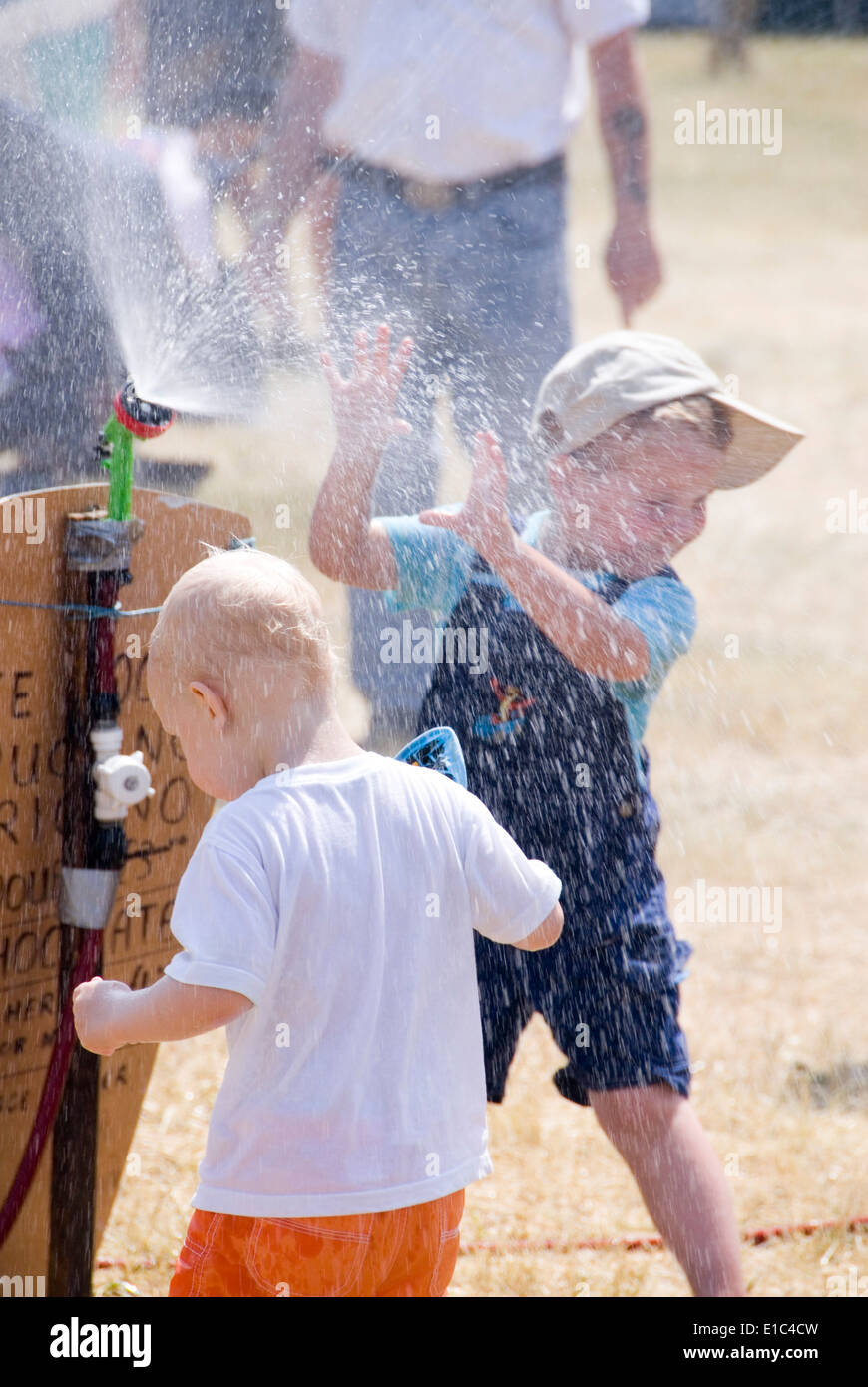 Tewkesbury Medieval Festival, Gloucester UK July 2013: children cooling off playing in water spray on a very hot Stock Photo
