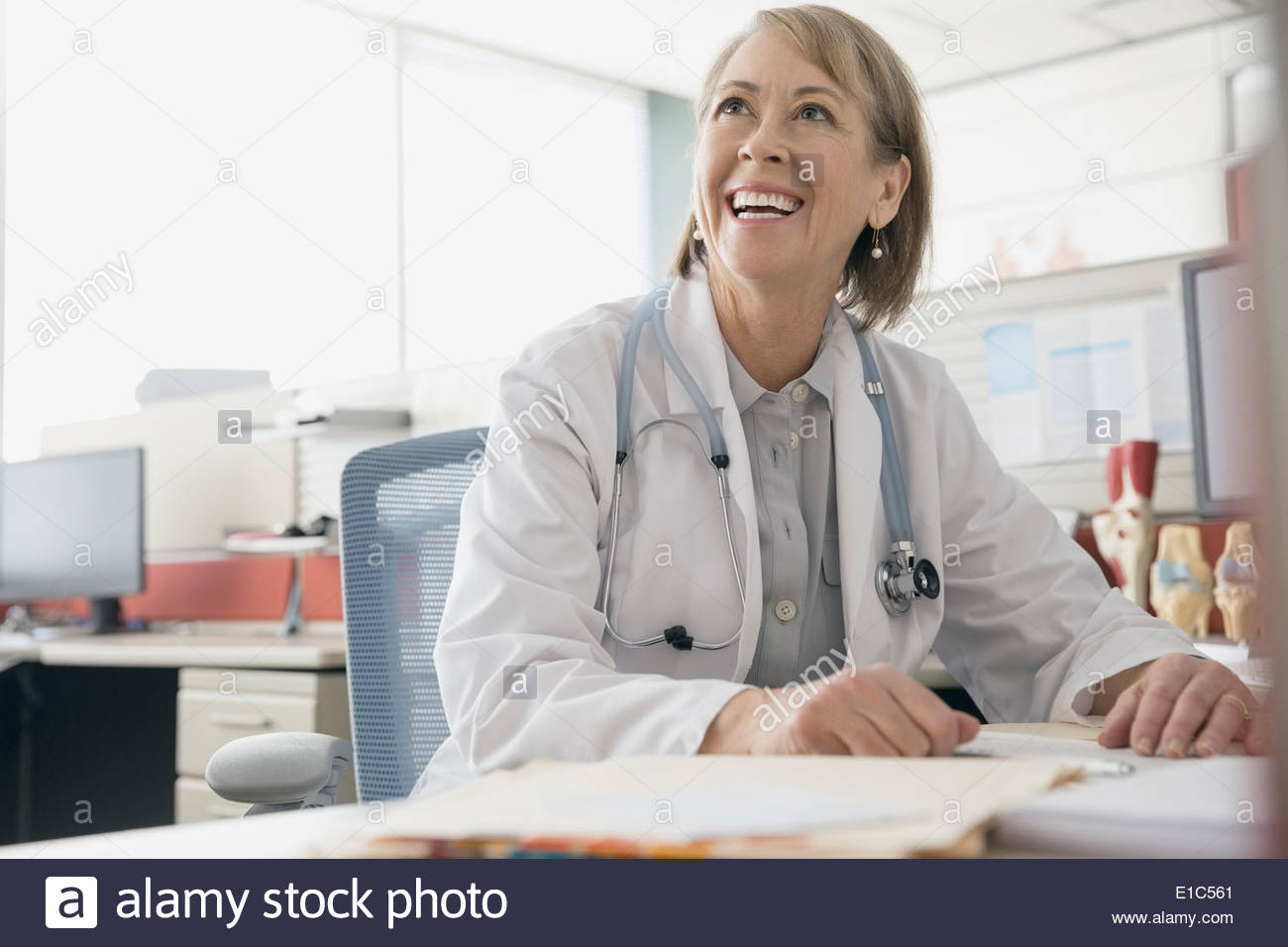 Smiling doctor working at desk - Stock Image