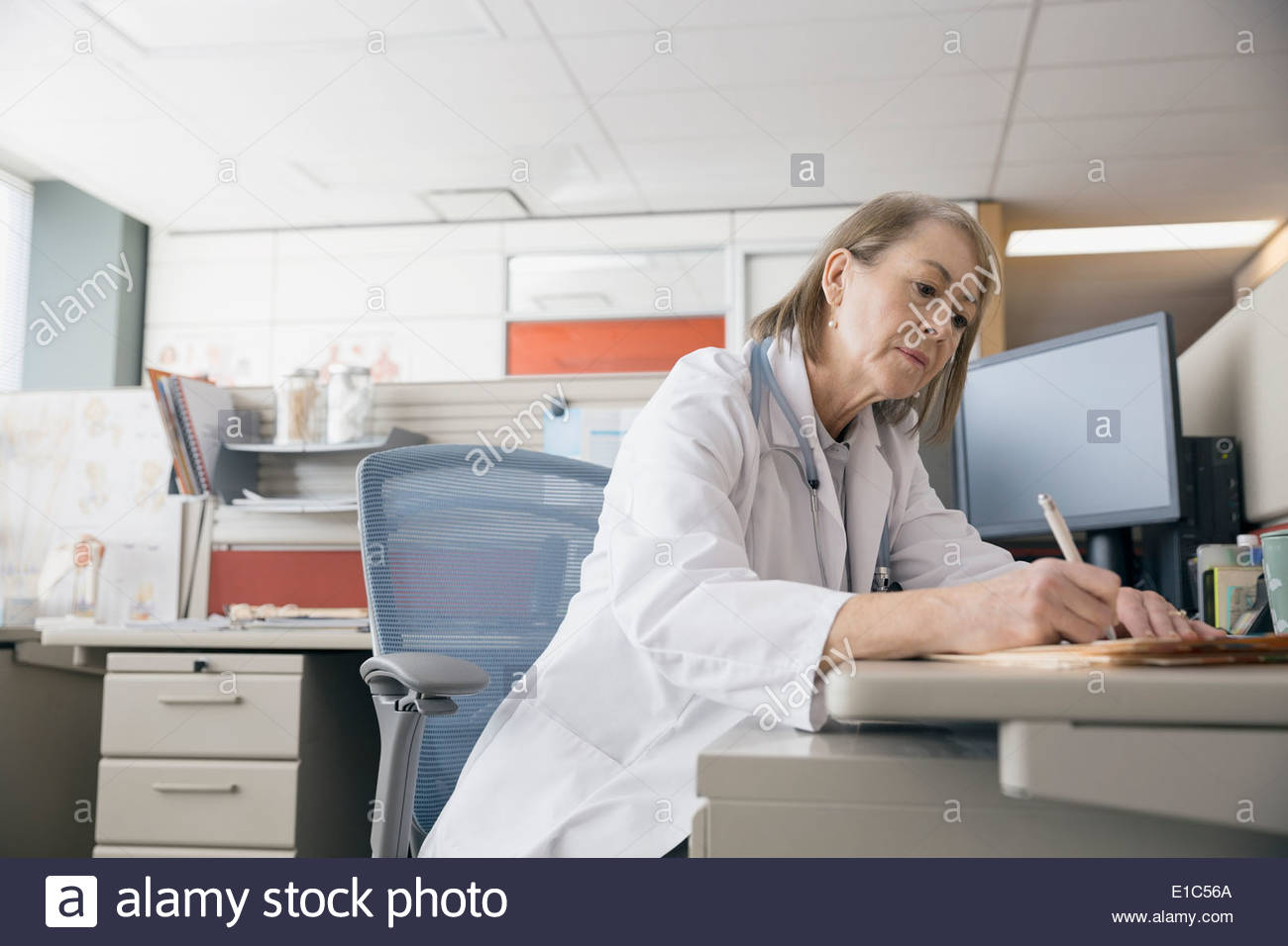 Doctor working at desk - Stock Image