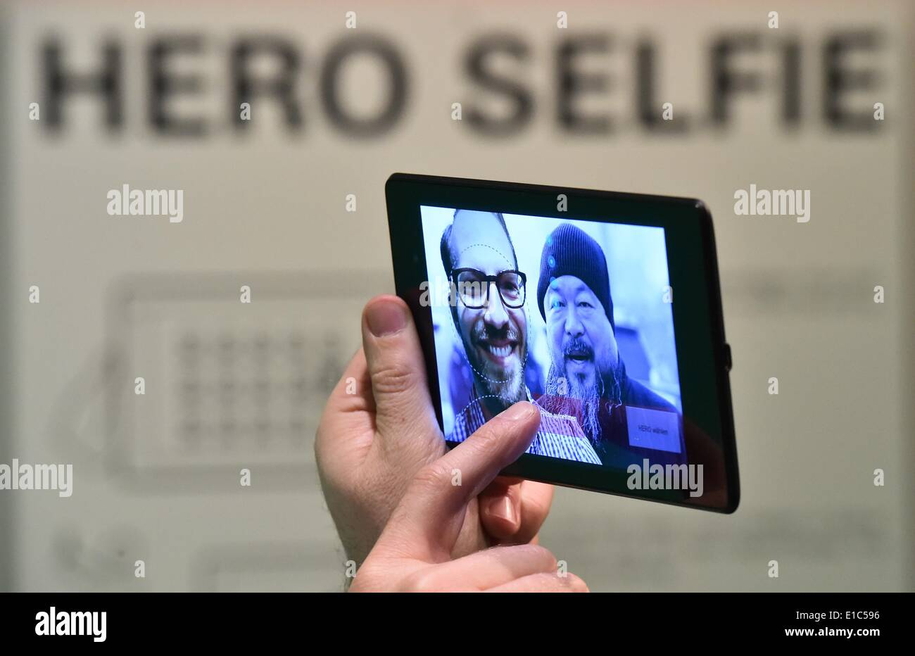 Neuhardenberg, Germany. 30th May, 2014. The co-creator of the exhibition Boris Hars-Tschachotin is pictured in the installation 'Hero Selfie' on the screen of a tablet next to the picture of the artist Ai Weiwei View in Neuhardenberg, Germany, 30 May 2014. The exhibition 'Remebering the heros - 200 years Neuhardenberg' (lit.) opens on 01 June 2014. Photo: Patrick Pleul/dpa/Alamy Live News - Stock Image
