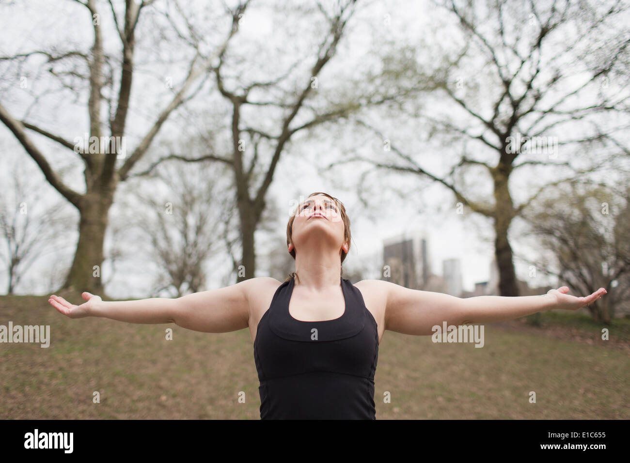 A young woman in Central Park, in a black leotard and leggings, doing yoga. - Stock Image