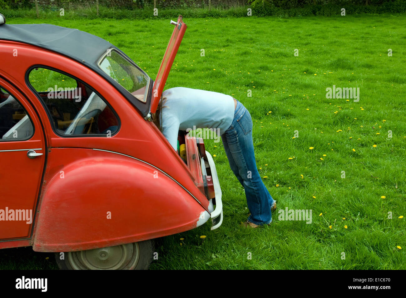 A  person leaning in to the boot at the rear of the car. - Stock Image