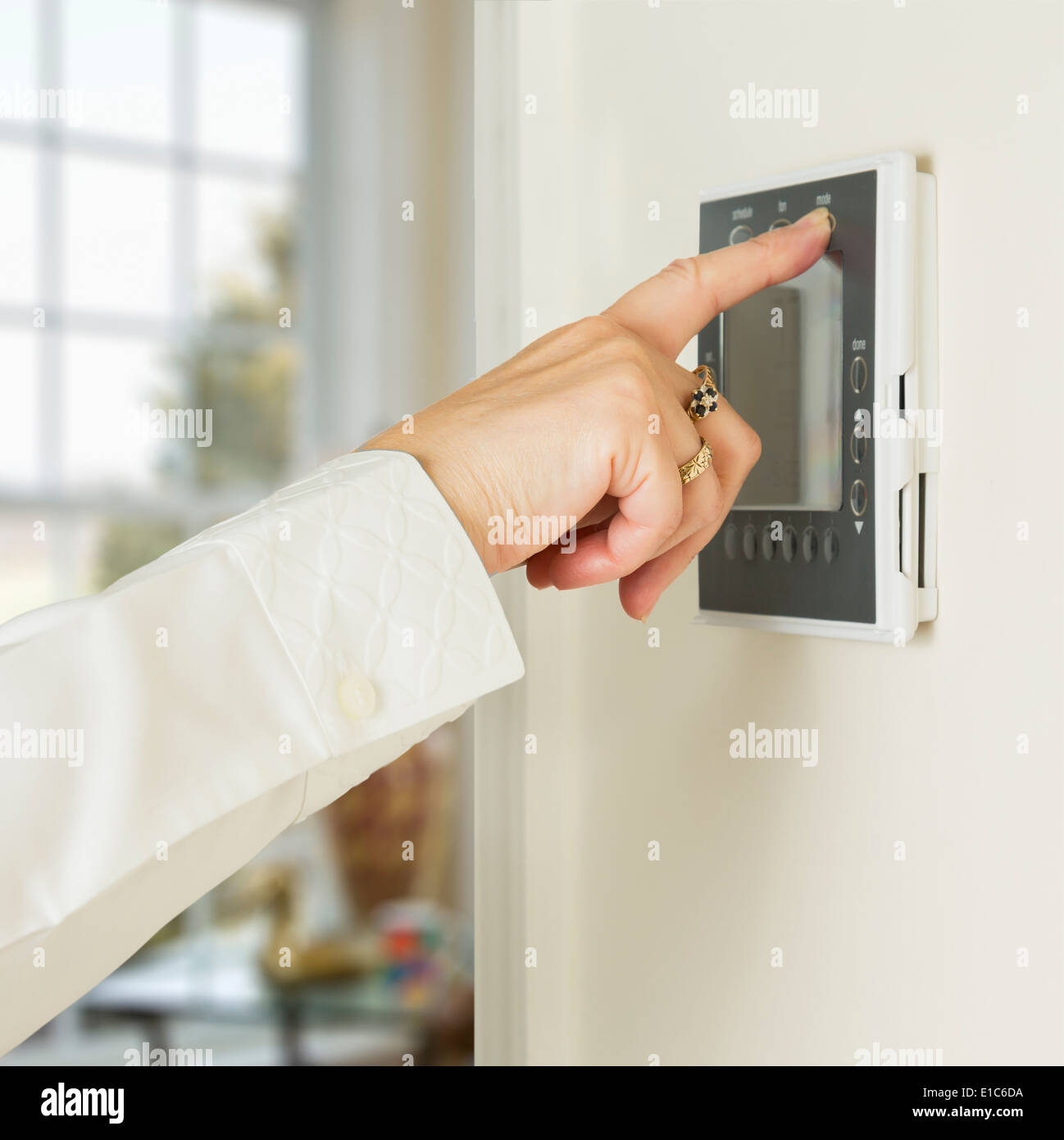 Using an electronic digital ventilation and heating thermostat timer on wall of a modern home - Stock Image