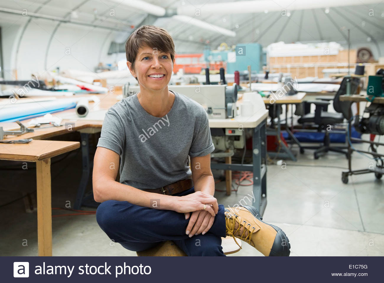 Smiling worker in textile manufacturing plant Stock Photo