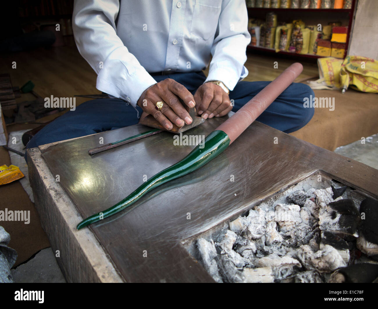 India, Rajasthan, Jodhpur, craftsman making green lac bangle, rolling the heated lac over charcoal fire - Stock Image