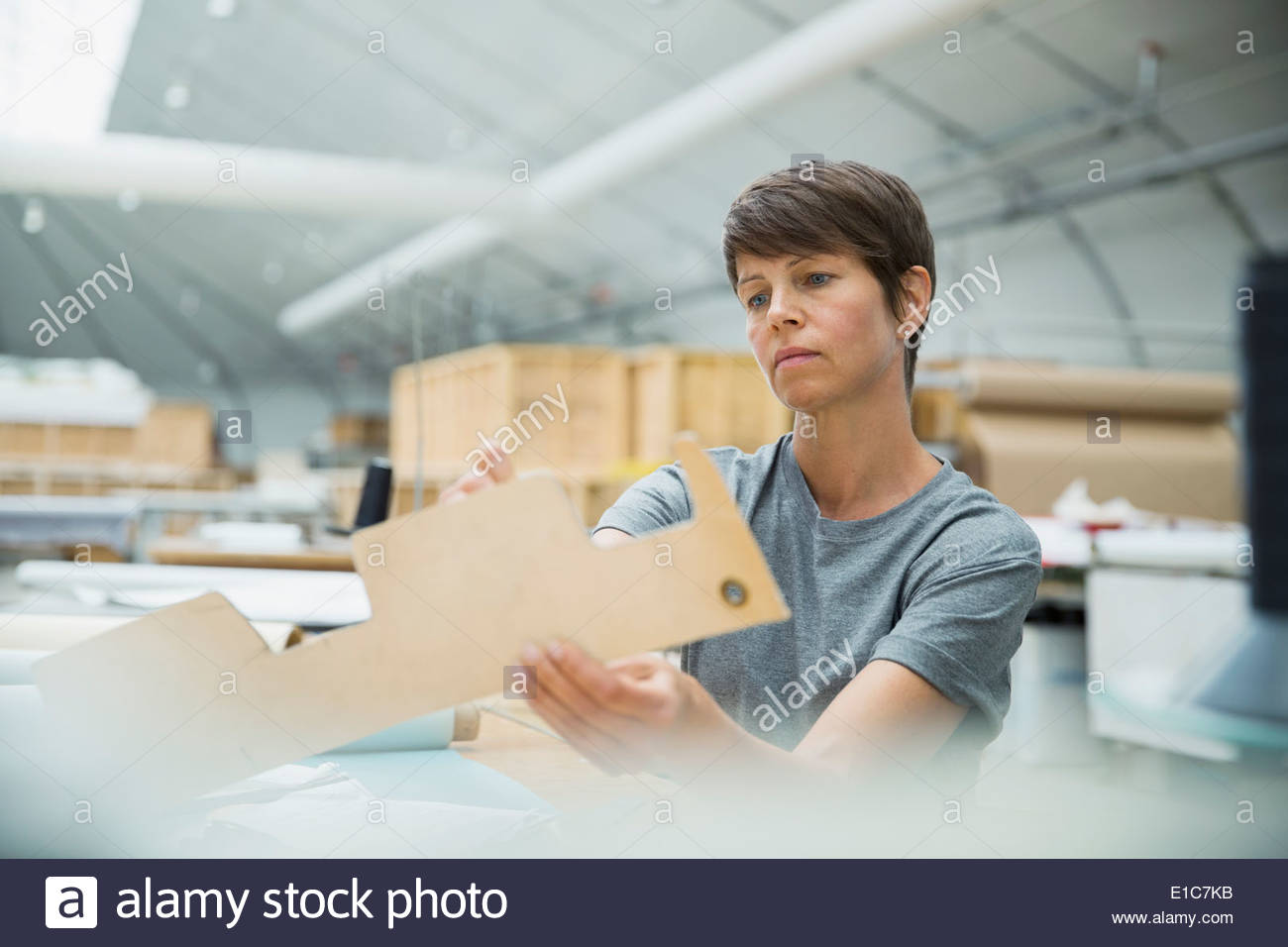 Worker examining form in textile manufacturing plant - Stock Image