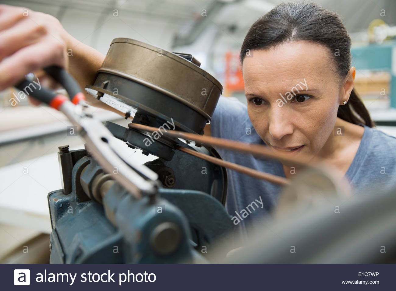 Worker using machinery in textile manufacturing plant - Stock Image