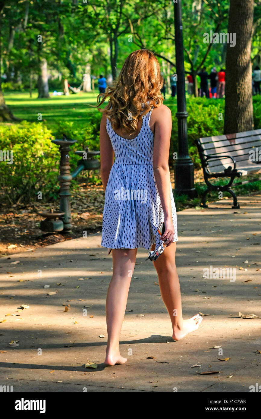 6b81665d530 A young teenage souther girl walks through Forsyth Park barefoot on an  early summer s evening -