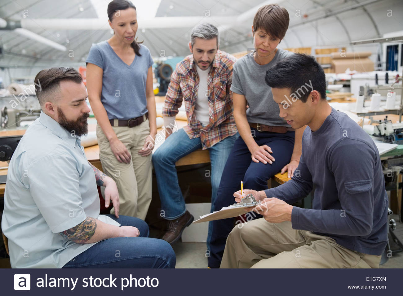 Workers meeting in textile manufacturing plant - Stock Image
