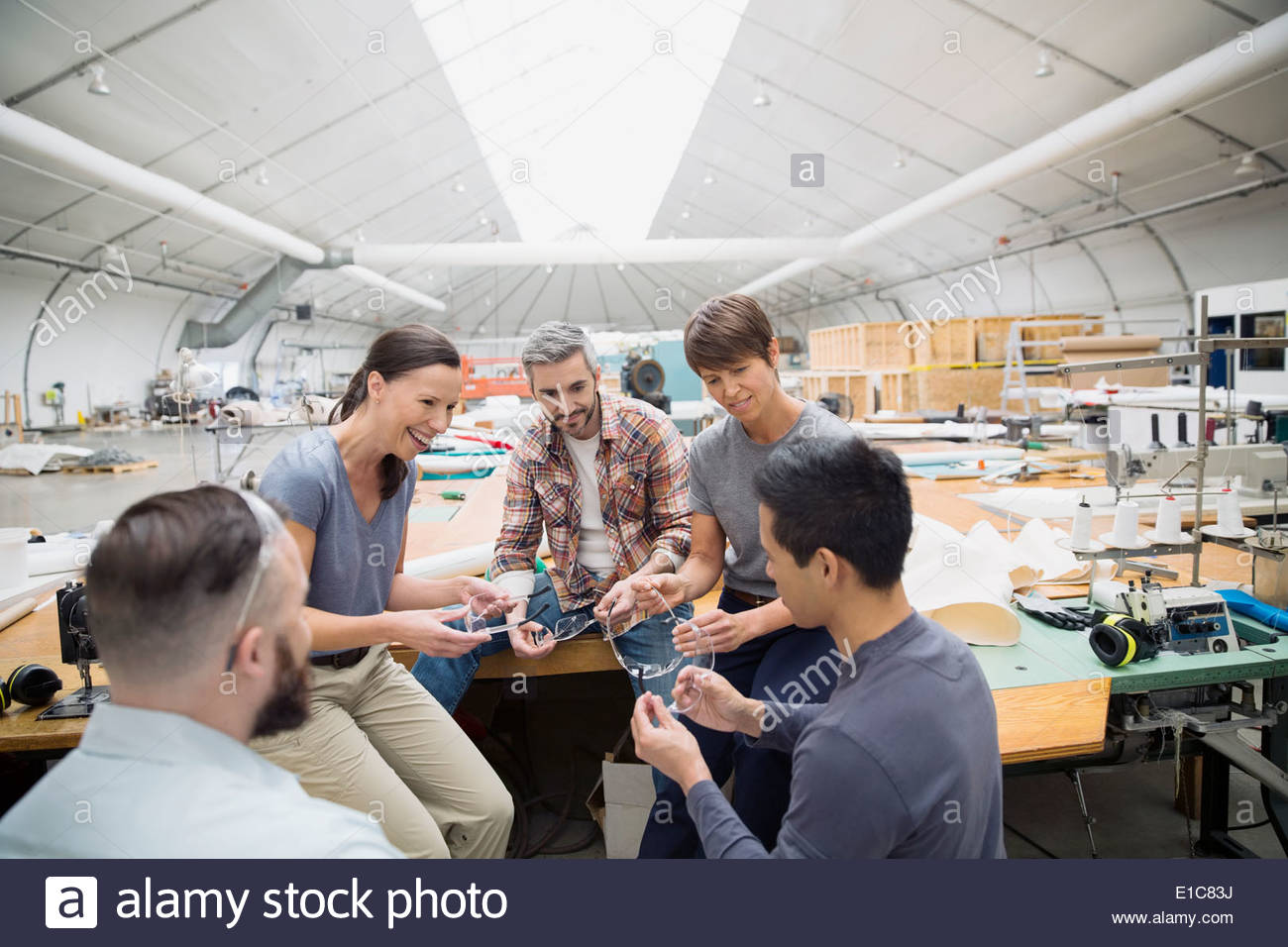 Workers with protective eyewear in textile manufacturing plant - Stock Image