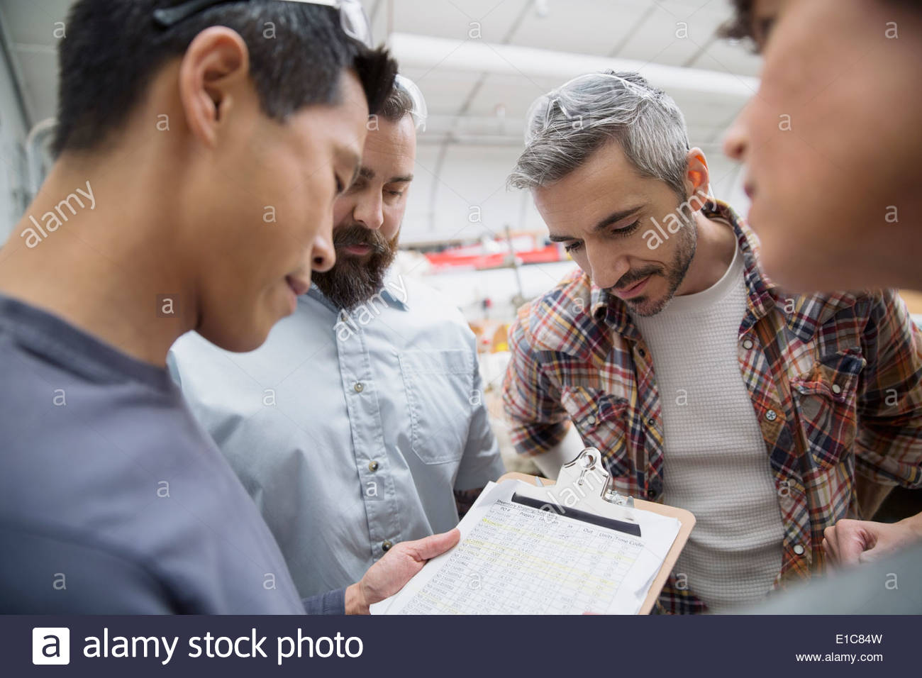 Workers with clipboard meeting in textile manufacturing plant - Stock Image