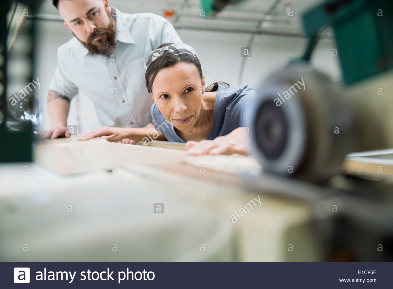 Workers using machinery in textile manufacturing plant - Stock Image
