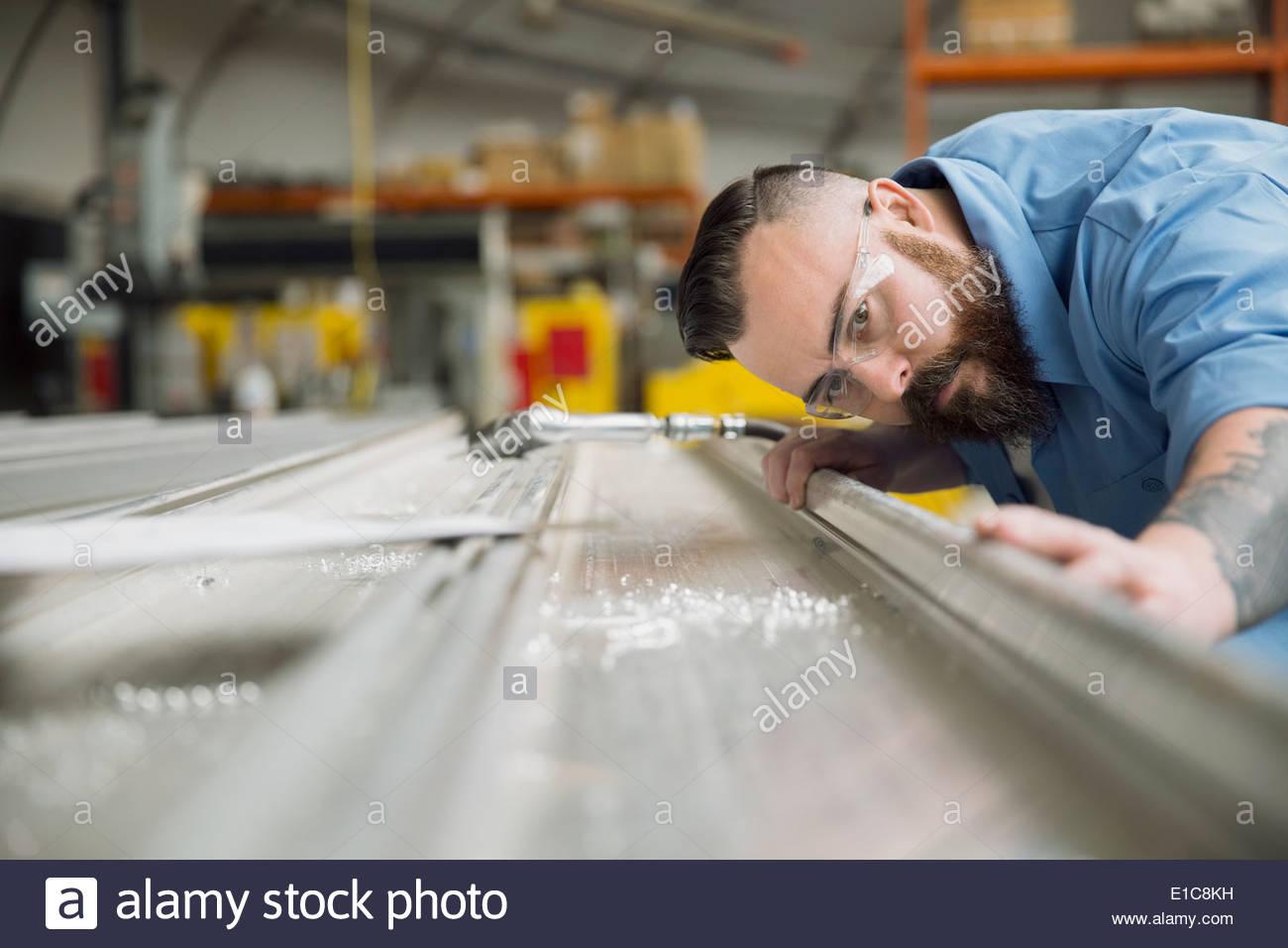 Worker examining sheet metal in manufacturing plant - Stock Image