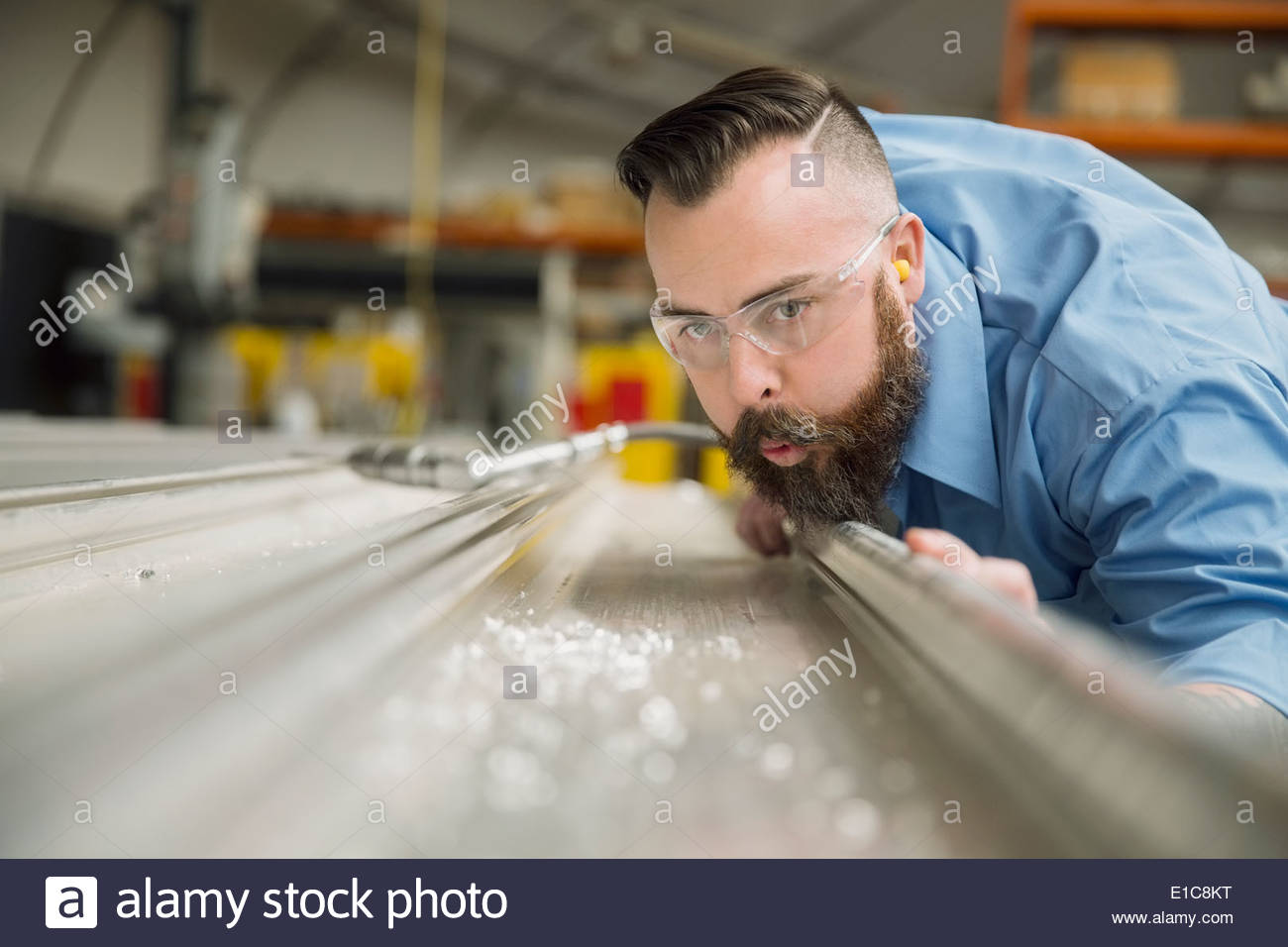 Worker blowing shavings from metal in manufacturing plant - Stock Image
