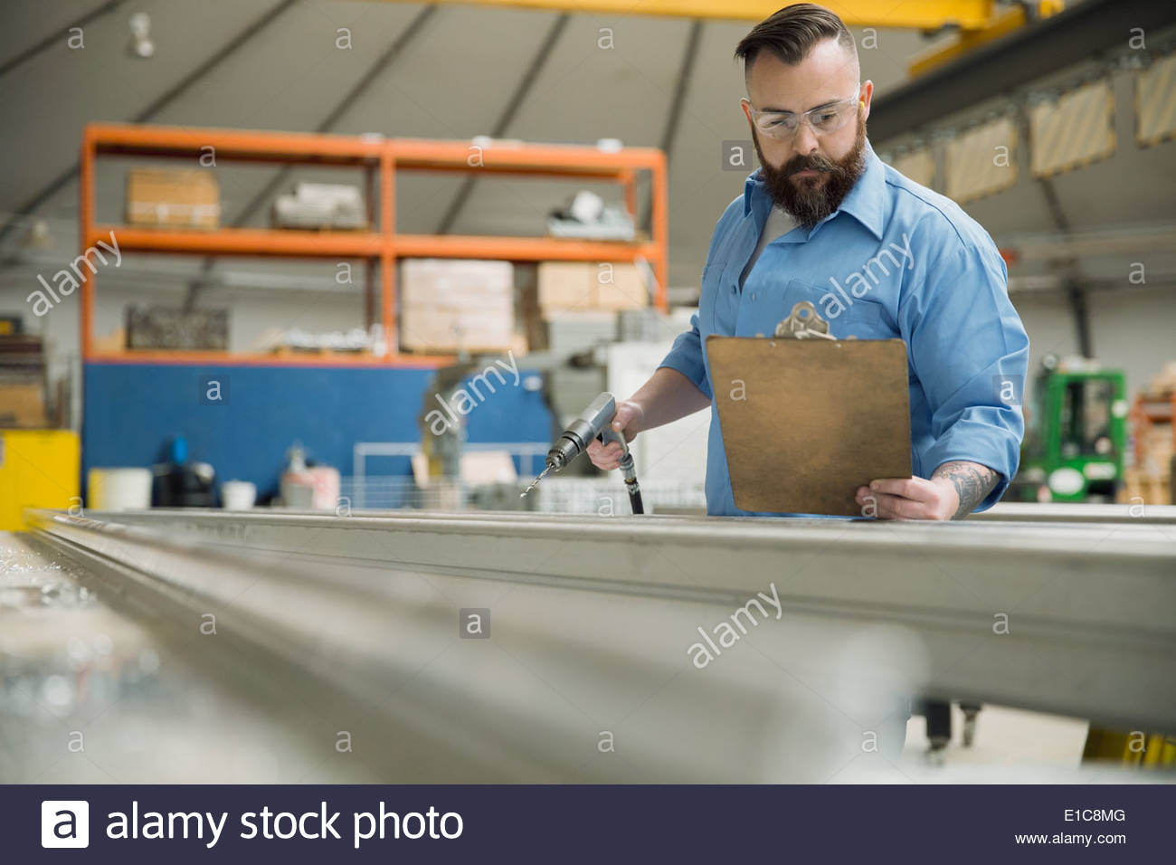 Worker with drill in manufacturing plant - Stock Image
