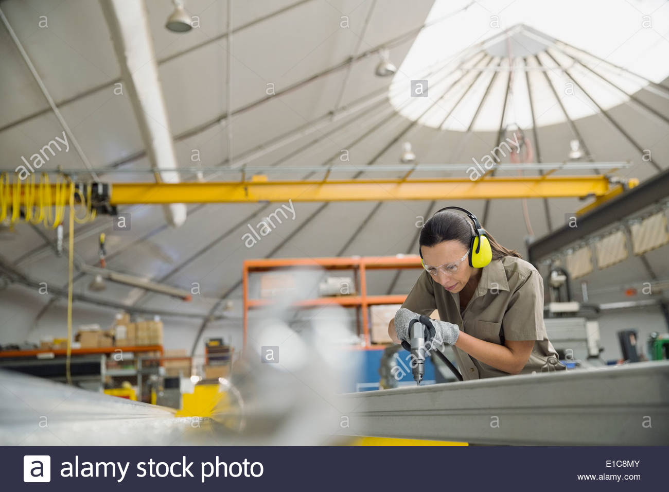 Worker drilling into metal in manufacturing plant - Stock Image