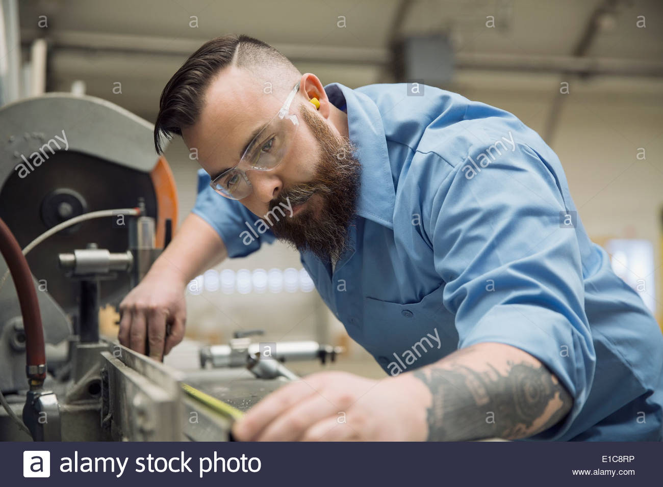 Worker operating machinery in manufacturing plant - Stock Image