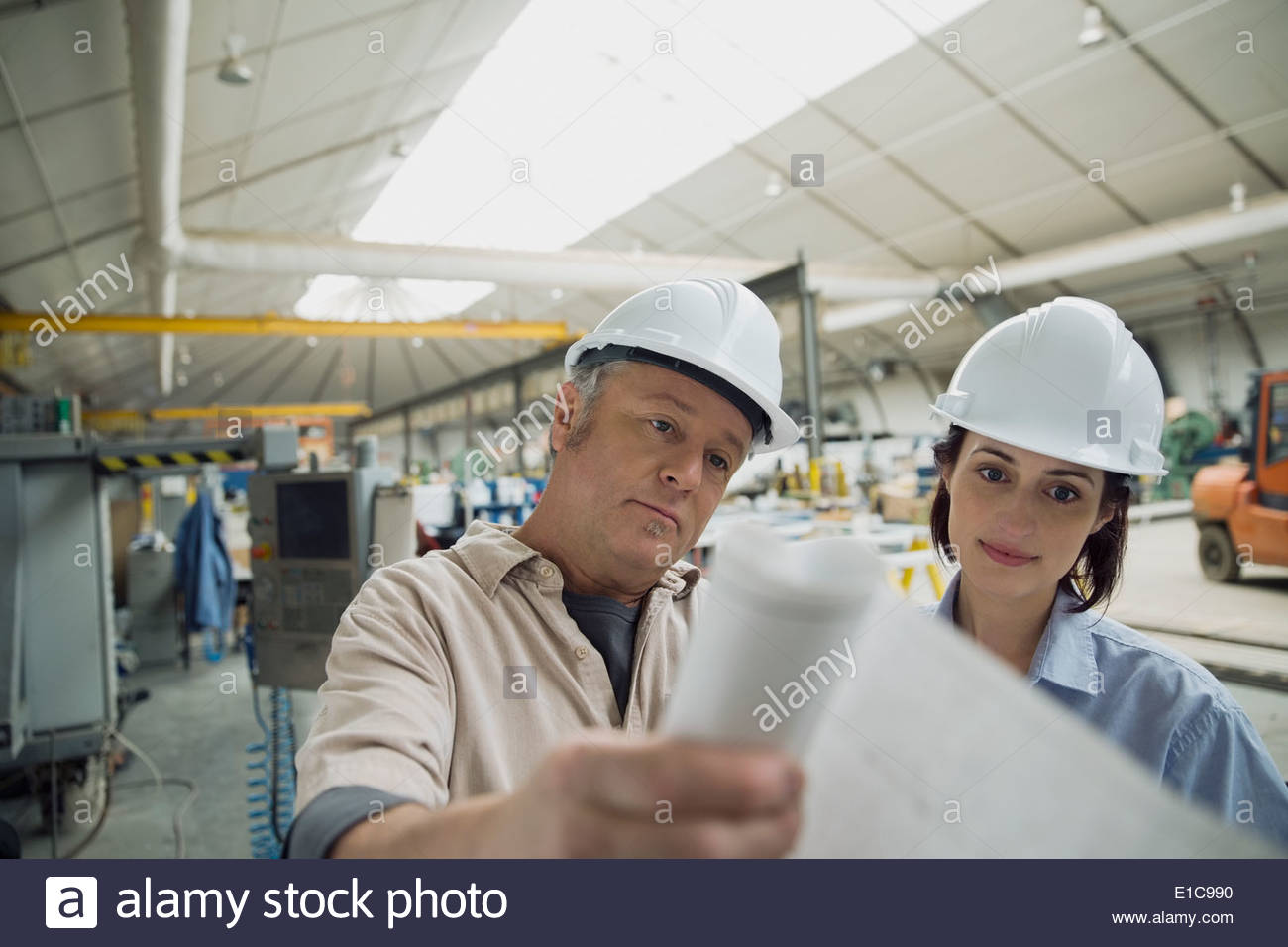 Workers reviewing blueprints in manufacturing plant - Stock Image