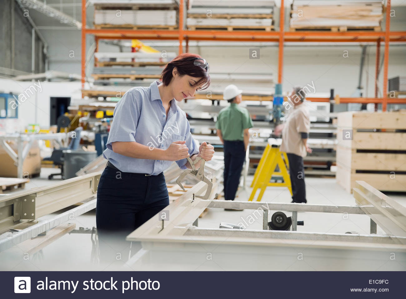 Worker using vise grip tool in manufacturing plant - Stock Image