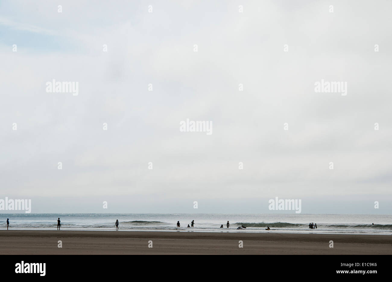 People in silhouette hanging out at Short Sand Beach, Oregon. - Stock Image