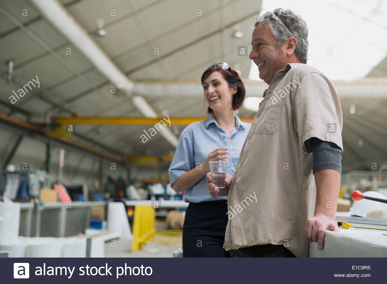 Workers talking in manufacturing plant - Stock Image