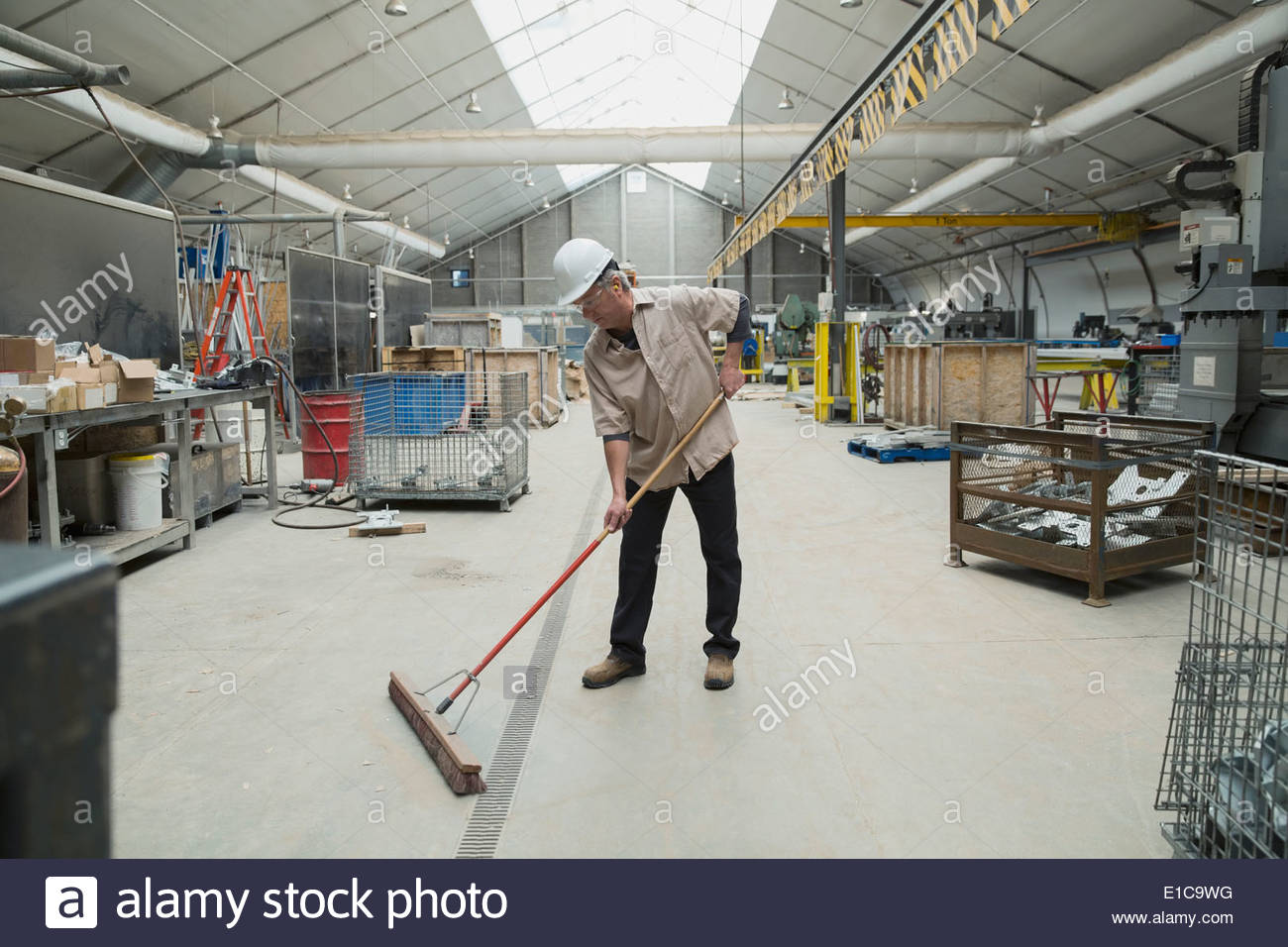 Worker sweeping in manufacturing plant - Stock Image