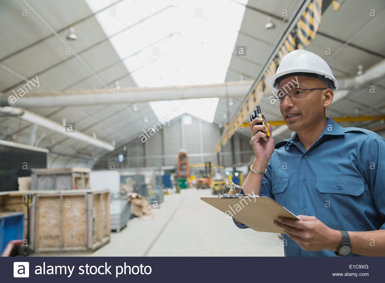 Worker using walkie-talkie in manufacturing plant - Stock Image
