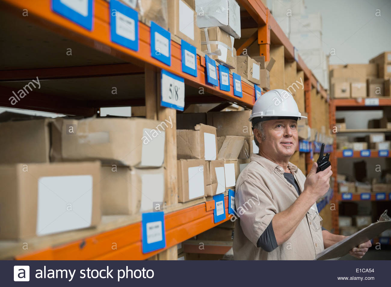 Worker with walkie-talkie in warehouse - Stock Image