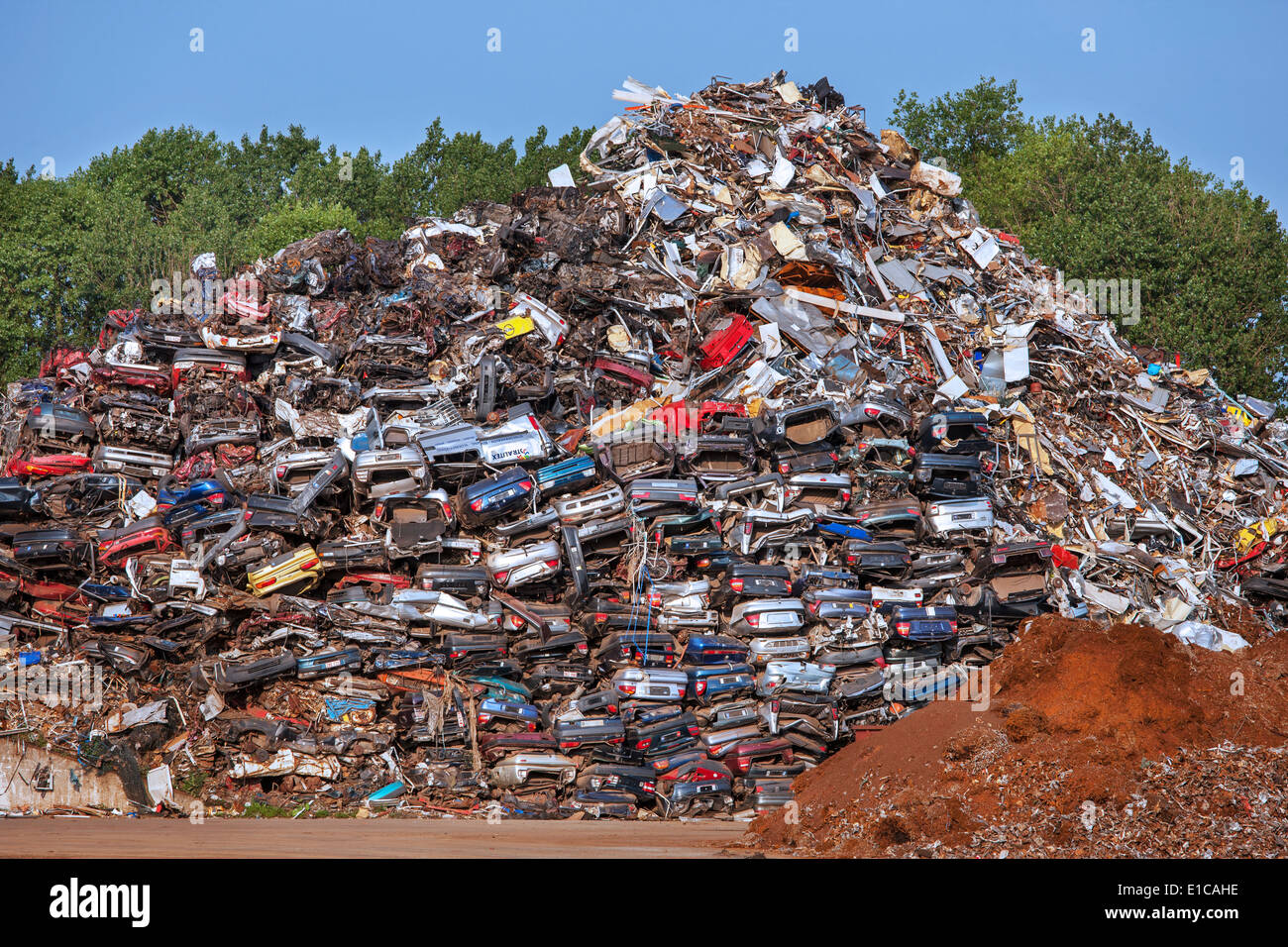 Cars piled up for recycling into scrap metal at junkyard - Stock Image