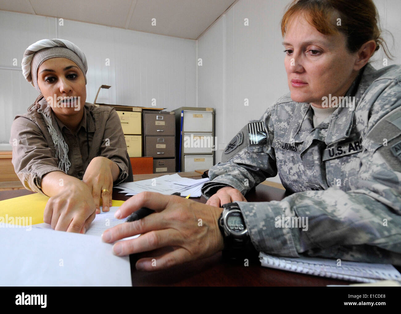 U.S. Army Capt. Sandra Jones, from Charlie Company, 422nd Civil Affairs Battalion, listens as an interpreter translates a polic - Stock Image