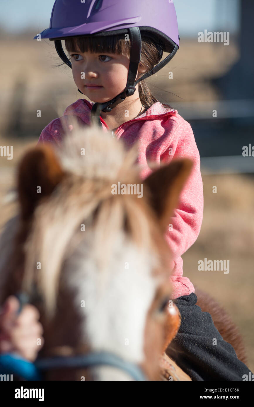 A 6 year old cowgirl rides a little pony just her size. - Stock Image