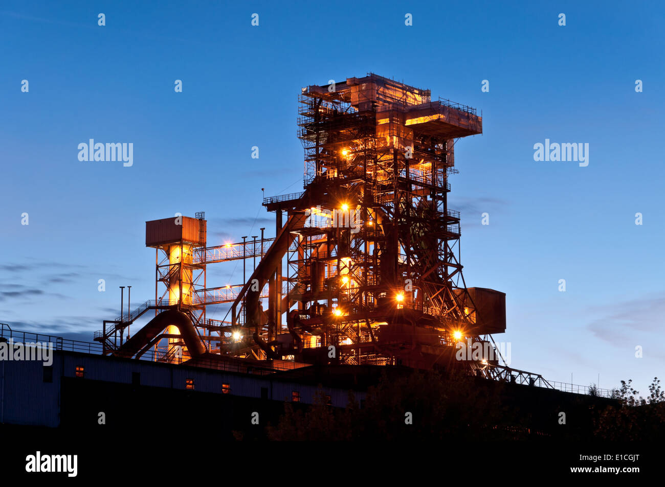 Lighted blast furnace at night in Germany  industrial plant blast furnace - Stock Image