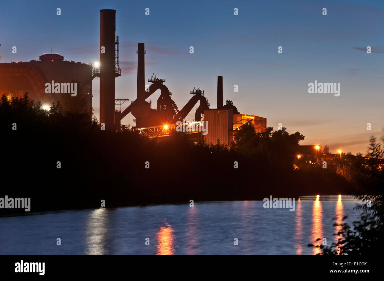 Lighted industrial plant of the steel industry  Water Reflection at night - Stock Image