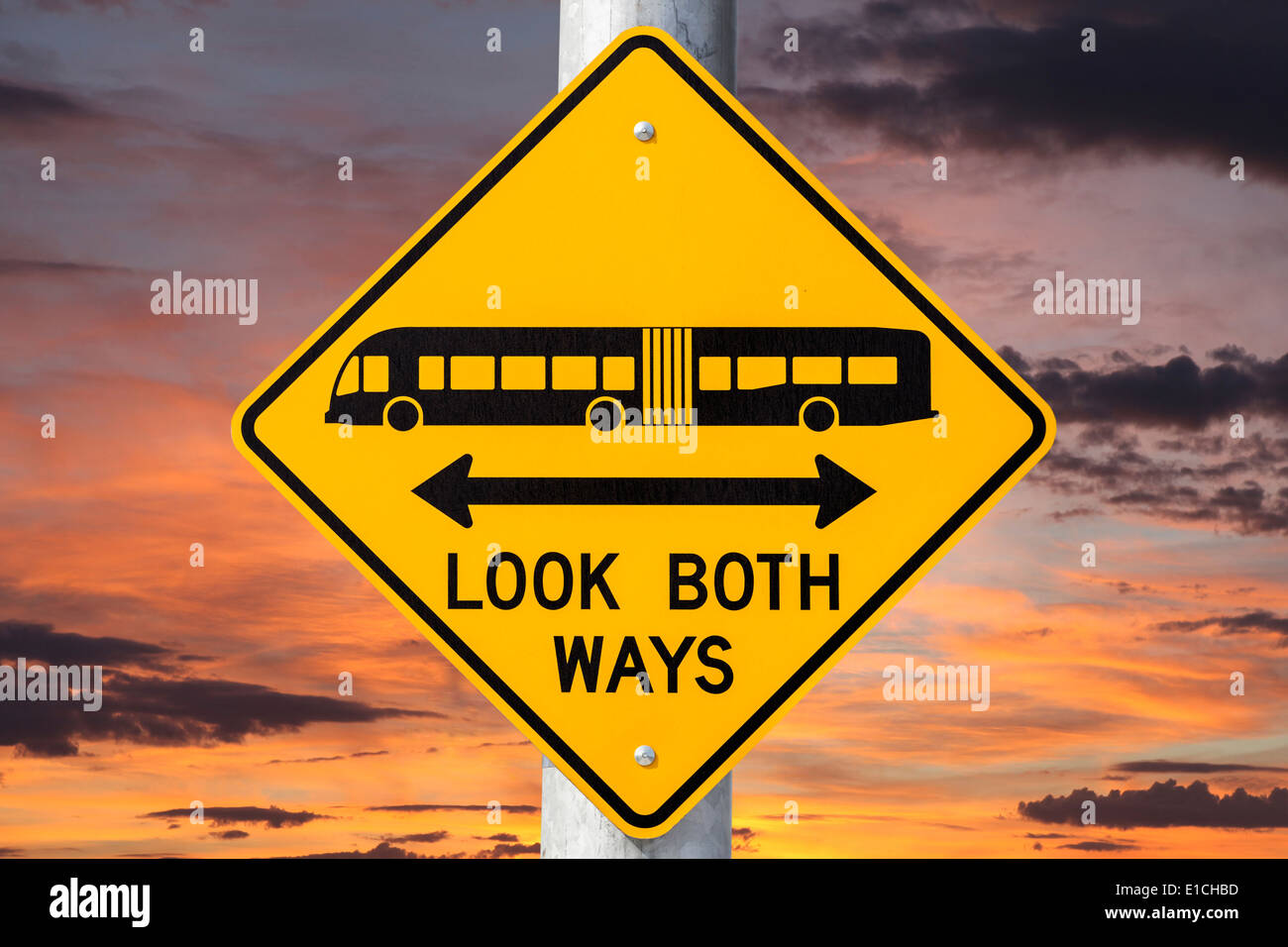Look both ways bus and tram warning sign with sunset sky. - Stock Image