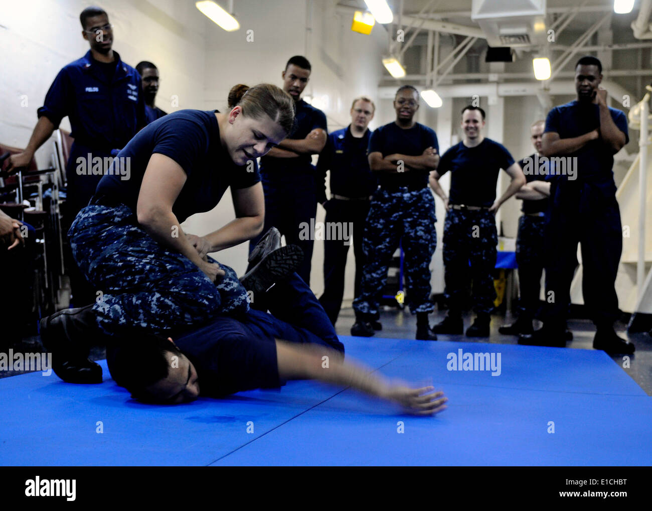 U.S. Navy Master-at-Arms 1st Class Amber Mathwig, left, demonstrates the proper technique to subdue a hostile attacker during a Stock Photo
