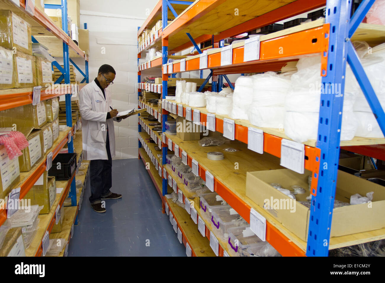 A South African employee taking stock of inventory among rows of shelves in a warehouse. - Stock Image