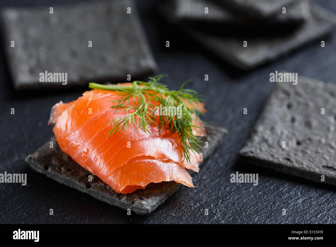 Smoked Salmon on black cracker - Stock Image