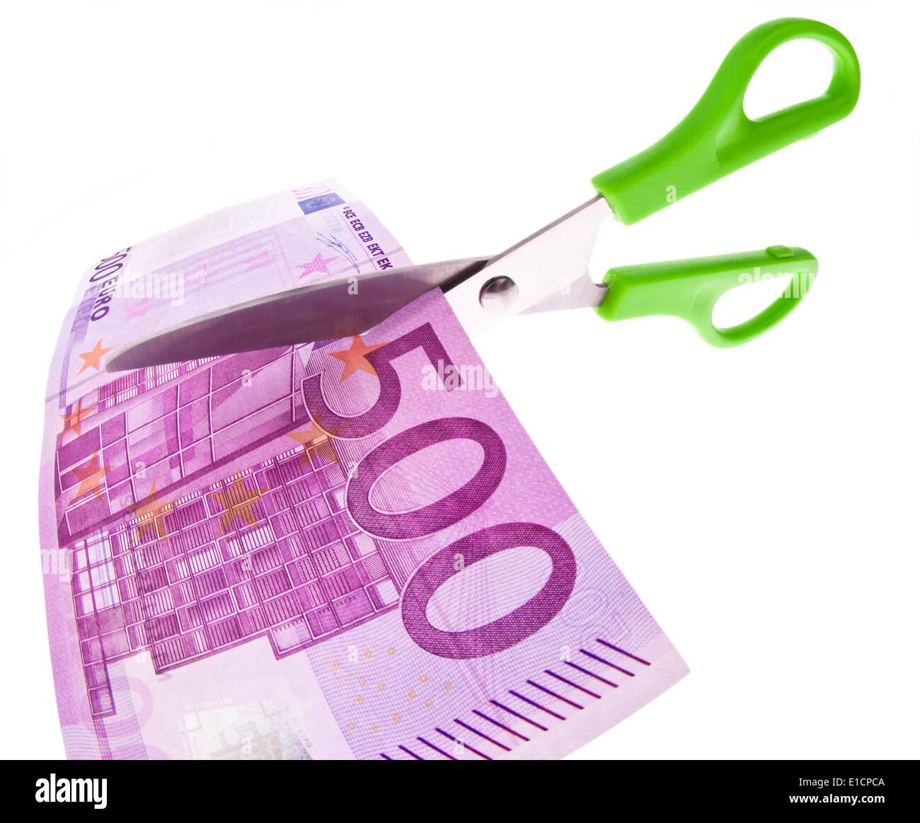From an Euro banknote a piece is cut with scissors. Symbol taxes and fees. Stock Photo