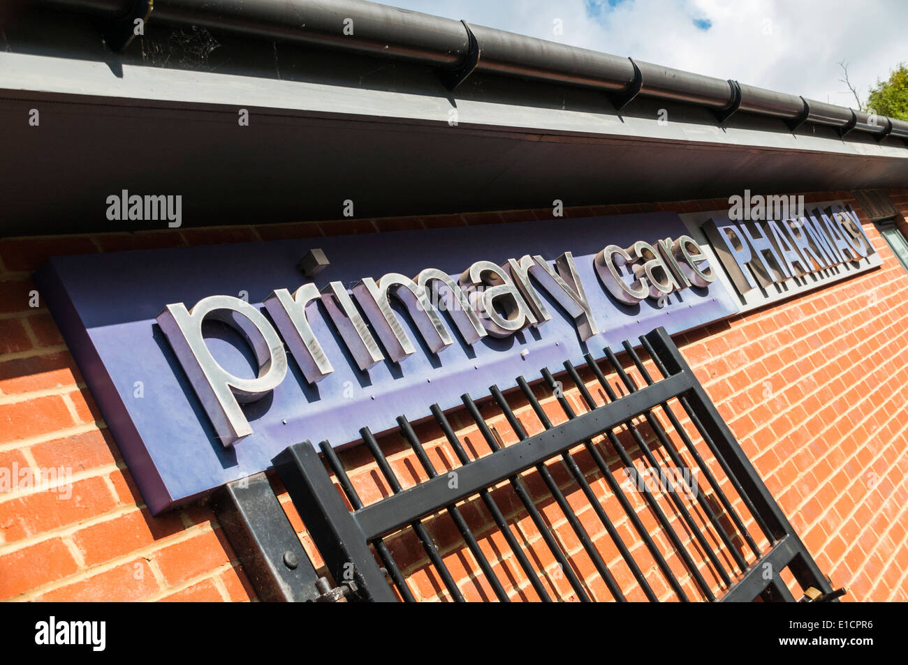 Primary Care Pharmacy sign on a brick wall outside an NHS pharmacy - Stock Image