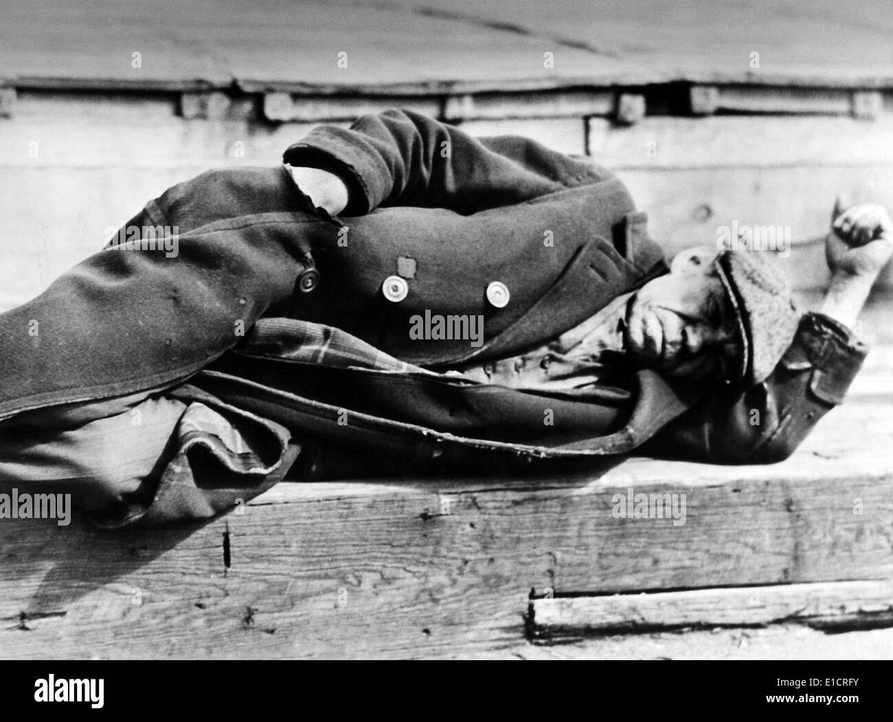 The Great Depression. Idle man dressed in worn coat lying down on a pier at the New York City docks: photo by Lewis W, Hine, - Stock Image