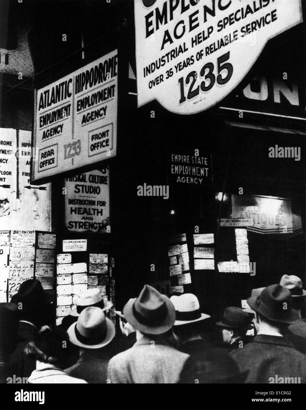 The Great Depression. Unemployed men crowd around the listings at a job board. 1930s - Stock Image