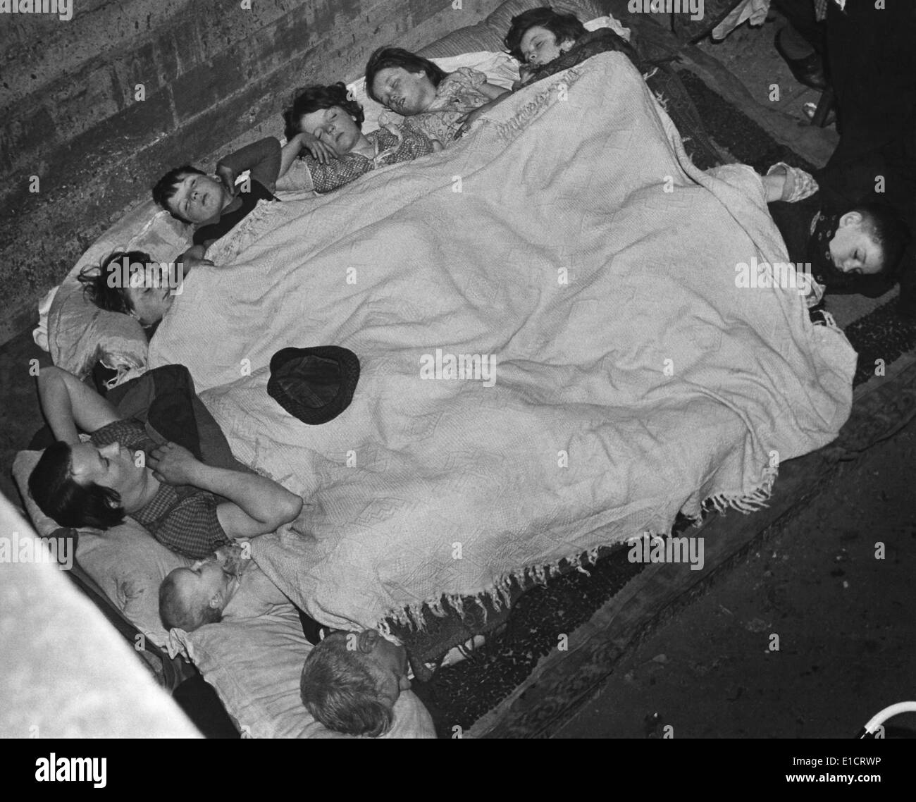 World War 2, Battle of Britain. A woman and eight children share a blanket in a southeast London subway station bomb shell - Stock Image