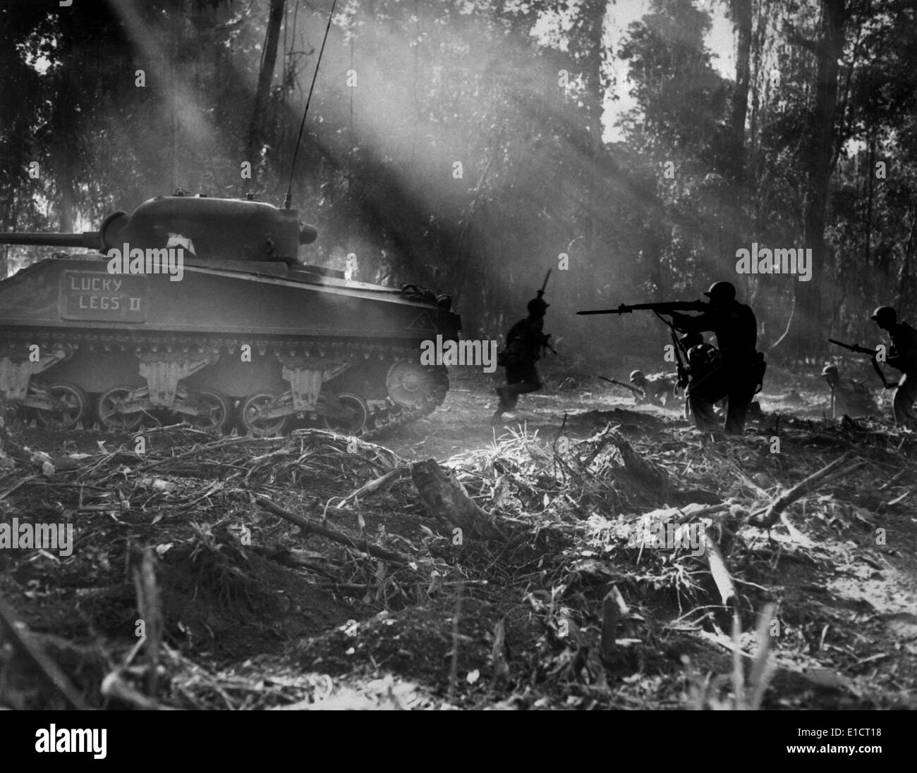U.S. soldiers advance in the cover of a tank on Bougainville, March 1944. At night Japanese troops would infiltrate American - Stock Image