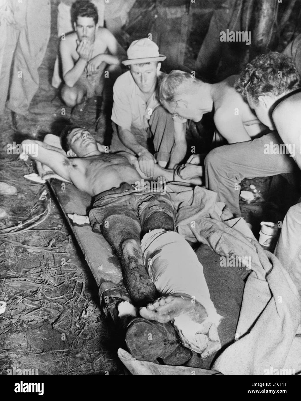 A wounded American soldier gets a blood transfusion in New Guinea jungle. The U.S. Army was fighting against the Japanese - Stock Image