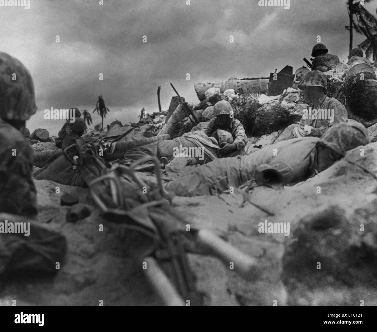 U.S. Marines take cover from Japanese fire behind a sea wall on Red Beach #3, Tarawa Island. Nov. 20, 1943. (BSLOC_2013-12_188) - Stock Image