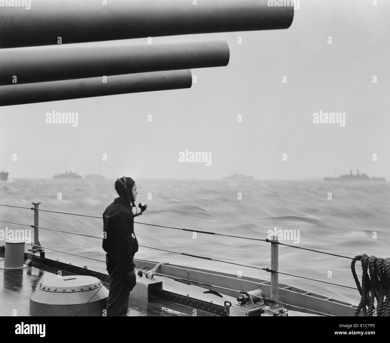 A sailor on a warship keeps alert watch over merchant ships in a convoy. U.S. warships protected convoys of 30 to 70 ships on Stock Photo